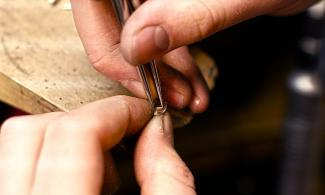 Close-up photo of hands working with silver