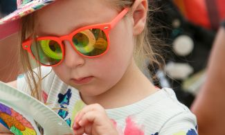 Child with ammonite reflecting in her sunglasses