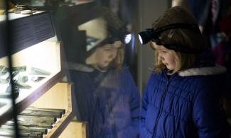 Girl using her head torch to look at what's on display