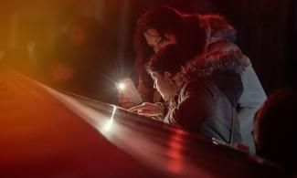 A girl looking at a display with her mum, using her phone as a torch