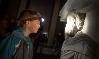 A boy wearing a head-torch looking at a classical statue