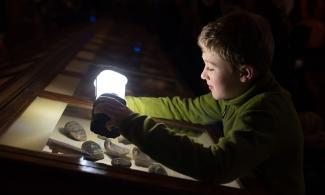 Boy using lantern to look at Museum display